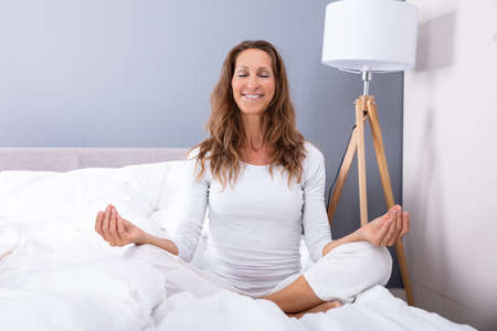 Smiling Matured Woman Sitting On Bed And Meditating With Eyes Closed