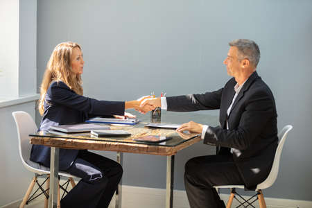 Smiling Mature Businessman Shaking Hand With Female Candidate Over Desk At Workplace
