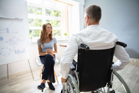 Rear View Of Disabled Businessman In Meeting At Workplace