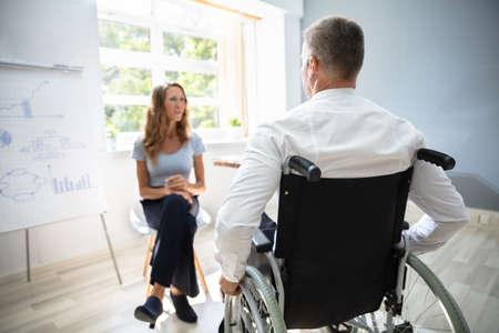 Vista trasera del empresario discapacitado en reunión en el lugar de trabajo