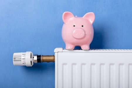 Sparschwein auf Heizkörper mit Temperaturregler vor blauem Hintergrund