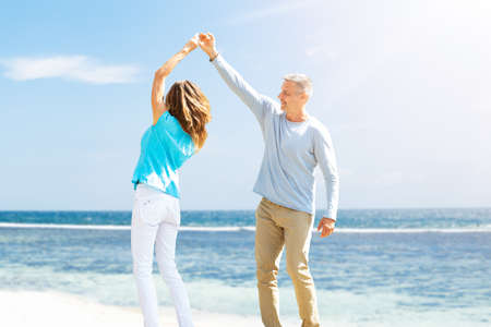 Portrait Of Happy Mature Couple Dancing On The Beach Banque d'images - 129473109