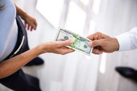 Close-up Of A Businesspersons Hand Taking Bribe From Partner