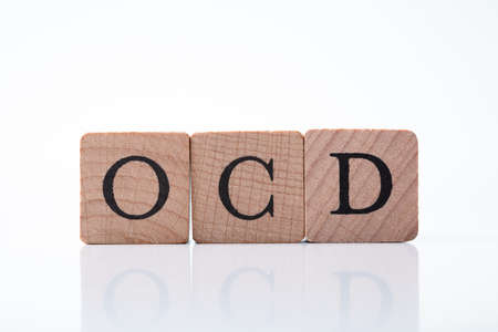 Close-up Of Ocd Text On Wooden Block Over Reflective Desk Banque d'images - 129473116