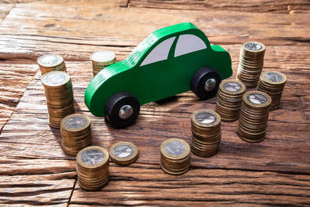 Green Wooden Car Near The Stack Of Coins On Wooden Desk Archivio Fotografico - 129473121