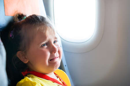 Little Girl Sitting Next To Mother Screaming On Airplane 写真素材