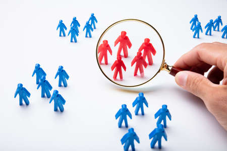 Hand Holding Magnifying Glass Over Red Human Figures Surround By Blue Human Figure Group