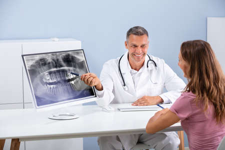 Dentist Explaining Showing Dental Panorama X-ray To Woman