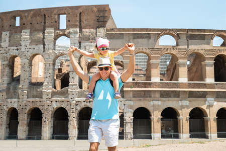 Young Tourist Family Standing In Front Of Colosseum In Rome, Italy