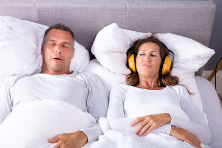 Mature Woman Covering Her Ears With Headphone While Man Snoring In Bed Standard-Bild
