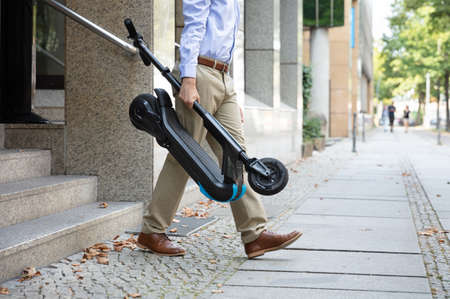 Man Carrying E-Scooter From Work Walking Out Of Office Building