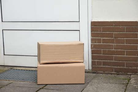 Stack Of Brown Cardboard Boxes Delivered At Doorstep