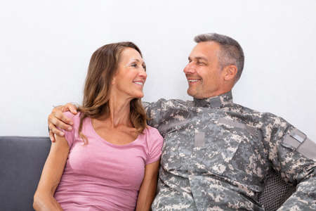 Smiling Soldier With His Wife Sitting On Sofa And Looking At Each Other