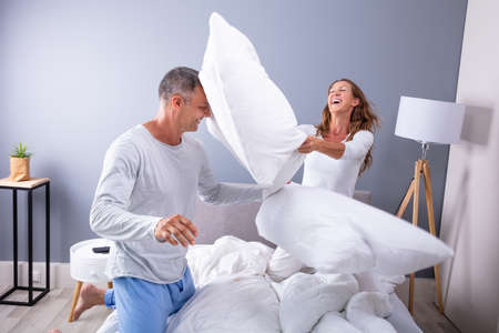 Happy Couple Fighting Together With White Pillows On Bed