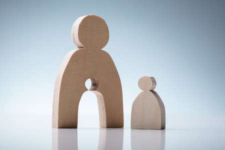 Wooden Figures Showing Mother And Child Concept Over Reflective Desk Stock fotó