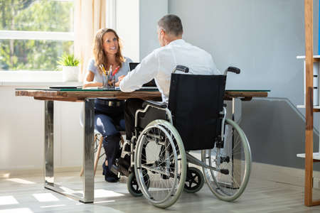 Rear View Of Disabled Businessman Working On Laptop With His Partner