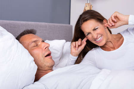 Angry Mature Woman Plugging Ear With Finger While Lying Near Snoring Husband In Bed Stockfoto