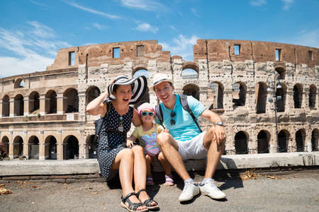 Young Tourist Family Sitting In Front Of Colosseum In Rome, Italy