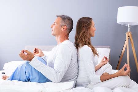 Matured Couple Sitting Back To Back On Bed Meditating Banco de Imagens