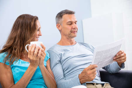Portrait Of Happy Mature Couple Reading Newspaper At Home Stock fotó