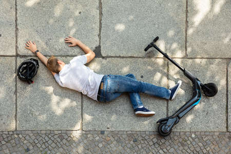 Unconscious Man Lying On Concrete Street After Accident With An Electric Scooter