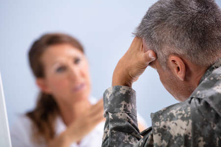 Mature Female Doctor Counseling Army Soldier Suffering From Stress In Clinic