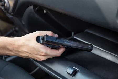Driver Taking Handgun From Glovebox Compartment Inside Car Banco de Imagens