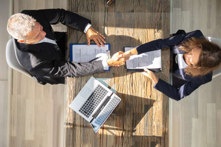 An Elevated View Of A Male Manager Shaking Hands With Female Applicant At Workplace