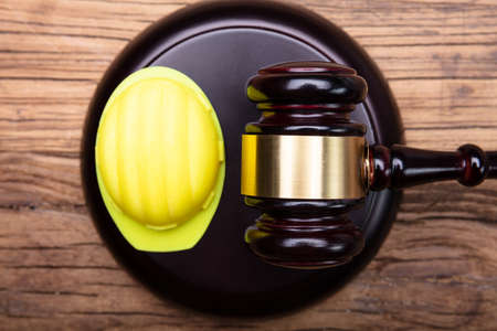 High Angle View Of Yellow Hard Hat And Gavel Arranged On Wooden Desk