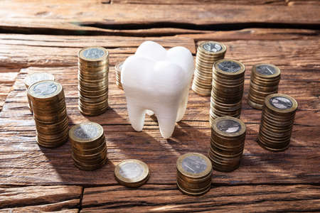 White Healthy Human Tooth And Stacked Coins On Wooden Desk Stock Photo - 129801723