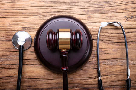 High Angle View Of Gavel With Stethoscope Arranged On Wooden Table