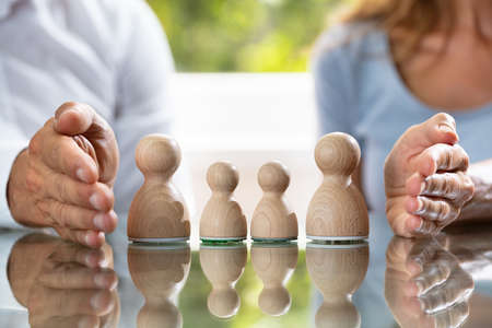 Close-up Of Couples Hand Protecting Wooden Pawn Family On Reflective Desk