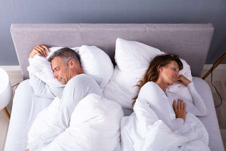 High Angle View Of Mature Couple Sleeping On Bed At Home Banco de Imagens