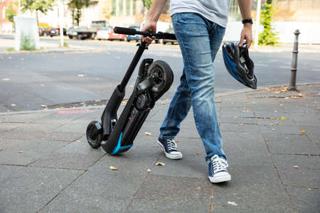 Man Carrying E-Scooter Walking On Street To Work Zdjęcie Seryjne