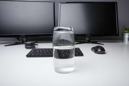 Glass Of Pure Water With Computer Desktop On White Desk