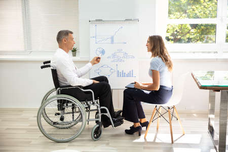 Disabled Matured Businessman Showing Diagram While Giving Presentation To His Colleague In Office Stock fotó