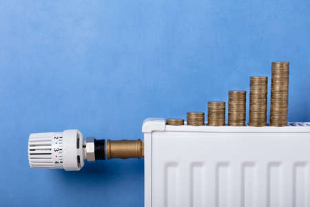 Stacked Of Coins Arrange In Row On Radiator In Front Of Blue Wall
