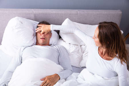 Frustrated Matured Woman Trying To Stop Mans Snoring With Her Finger While Sleeping On Bed