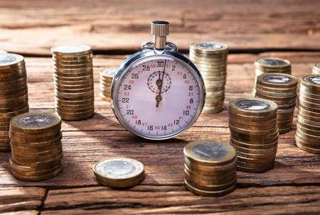 Stacking Golden Coins On Desk Near Stopwatch Over Wooden Desk