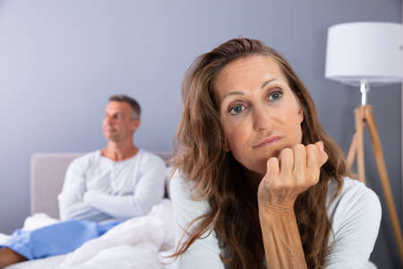 Unhappy Mature Couple Sitting On Bed In Bedroom