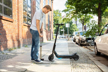 Man Pumping Air Into Tire On His E-Scooter