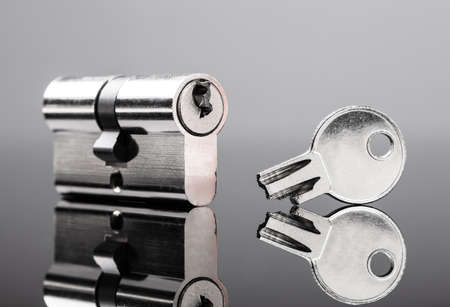 Close-up Of Pin Tumbler Of Cylinder Lock With Broken Key On Reflective Desk Stock Photo