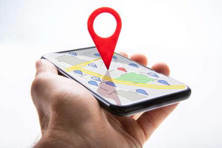 Close-up of a Person's Hand Holding Cellphone avec pointeur de carte rouge sur fond blanc Banque d'images