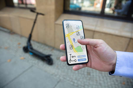 Young Man Using App To Rent Electric Scooter