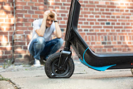 Stressed Man Looking At Flat Tire On His E-Scooter