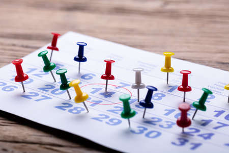 Calendar With Circular Mark Around 14 Number And Colorful Push Pins Over Wooden Desk Stok Fotoğraf