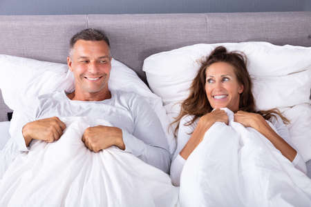 Happy Couple Lying On Bed With White Blanket In Bed Room