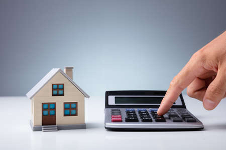 Person's Hand Calculating With Calculator Near House Model On Desk Stok Fotoğraf - 129802080