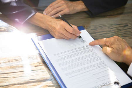 Close-up Of A Real Estate Agent Helping Client In Filling Contract Form