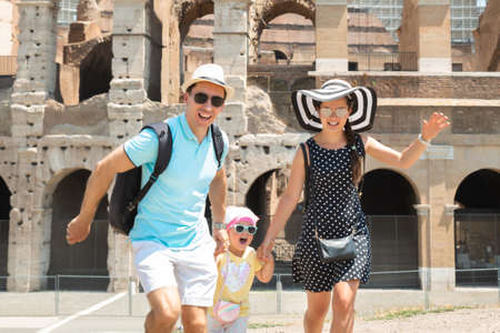 Young Tourist Family Running In Front Of Colosseum In Rome, Italy